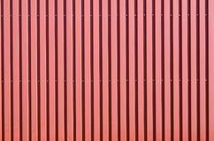 Red corrugated galvanised iron cladding. Colorful red corrugated galvanised iron cladding on a wall or fence in a full frame background architectural texture stock images