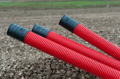 Red corrugated plastic pipes. On gravel background Royalty Free Stock Images