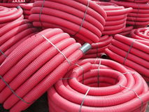 Red corrugated plastic pipes used for underground electrical lines.  Stock Photo