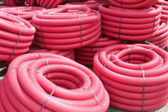 Red corrugated plastic pipes used for underground electrical lines Stock Photo