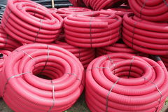 Red corrugated plastic pipes used for underground electrical lines.  Royalty Free Stock Photos
