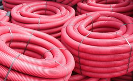 Red corrugated plastic pipes used for underground electrical lines.  royalty free stock photography