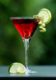 Red cosmopolitan cocktail. Red cocktail with blurry green background, beautifully arranged with pieces of lime Stock Images