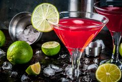 Red cosmopolitan cocktail with lime. In martini glass, on dark rusty background copy space stock photos