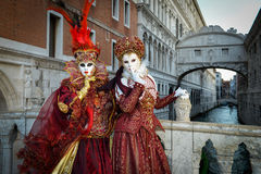 Red costumed masked women. Standing at the bridge of sighs in Venise at sunrise Stock Image