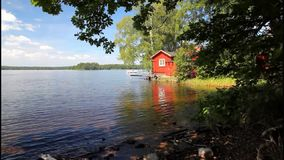 Red cottage by a lake stock video footage