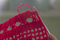 Red cotton tablecloth with crochet hook. Stock Photos