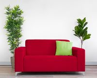 Red couch with green cushion and two plants in front of a blank white wall. Minimalist red two seat couch with one green cushion in front of blank wall with two stock photography