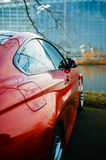 Red coupe car parked in front of river with European Parliament royalty free stock photography