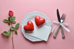 Red couple heart and greeting card on white dish, with fork and knife in ribbon, Rose, On pink background. stock photo