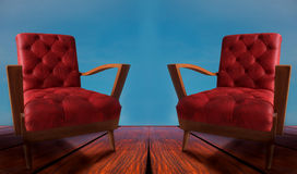 Red couples arm chairs on wood and blue background Stock Photography