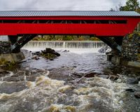 A red covered bridge first built in 1883 spans a rapidly flowing stock photos