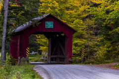 Red Covered Bridge and Gravel Road - Autumn / Fall - Vermont. A gravel road leads to a historic red painted covered bridge during a beautiful fall / autumn day Royalty Free Stock Photos