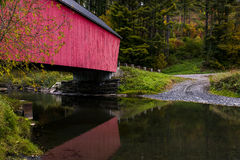 Red Covered Bridge and Gravel Road - Autumn / Fall - Vermont. A gravel road leads to a historic red painted covered bridge reflected in the still creek during a Stock Photography