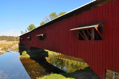 Red covered bridge over river Stock Image