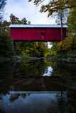 Red Covered Bridge and Pond - Autumn / Fall - Vermont. A historic red painted covered bridge is reflected in the still pond below during a beautiful fall / Royalty Free Stock Photo