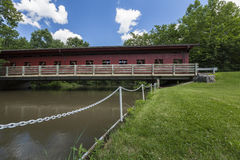 Red Covered Bridge. A red covered bridge spanning a river Stock Photos