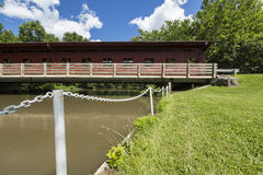 Red Covered Bridge. A red covered bridge spanning a river Stock Images