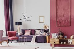 Red cozy living room. Red armchair next to a purple settee in cozy living room interior with wooden cupboard and lamp Stock Photography