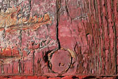 Red cracked paint on an old board, door hinge in the form of arr Stock Images