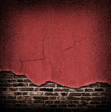 Red cracked rough plaster coming off the brick wall Stock Photo