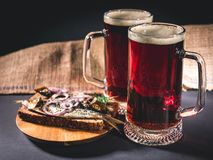 Red craft beer, hot smoked fish sandwich on a dark background. Low key lighting royalty free stock image