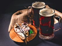 Red craft beer, hot smoked fish sandwich on a dark background. Low key lighting royalty free stock photos