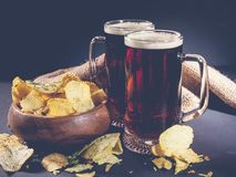 Red craft beer and potato chips in a wooden bowl on a dark background. Low key lighting royalty free stock images