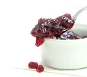Red cranberry jam dripping from a spoon over a small bowl, backg Royalty Free Stock Images