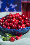 Red cranberry juice in a glass, cranberries in the blue clay bow. L on the table, blue wall Royalty Free Stock Images