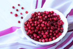 Red cranberry on pink napkin close up. Red cranberry and white plate on pink napkin close up Royalty Free Stock Photography
