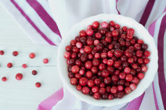 Red cranberry and white dish on pink napkin. Red, colored cranberry and white dish on pink napkin Royalty Free Stock Photography