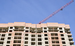 A red crane arrow over a high-rise building. A red arrow of a crane over a brick high-rise building Royalty Free Stock Photography
