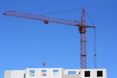 Red crane and blue sky on building site Stock Photo