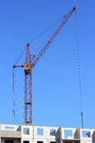 Red crane and blue sky on building site Stock Photos