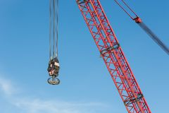 Red crane boom with hook against blu sky Stock Photo
