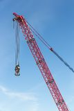 Red crane boom with hook against blu sky Stock Images
