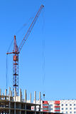 Red crane and part of building under construction Stock Photo