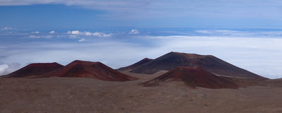 Red craters above the clouds on Mauna Kea summit Royalty Free Stock Photos
