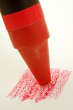 Red Crayon. A red crayon coloring on paper stock photo