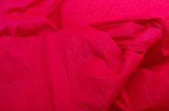 Red crepe paper christmas background / texture. With folds and creases Stock Photos