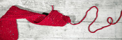 Red crocheted scarf on wooden table, handiwork, Header. And Banner Stock Photo