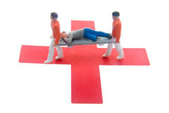 Red Cross. Miniatures carrying another on a stretcher on top of a red cross Royalty Free Stock Images