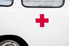 Red cross on ambulance. Close up of a red cross on a vintage ambulance Royalty Free Stock Photos