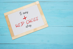 Red Cross Day , lettering on white desk, blue background Stock Photo