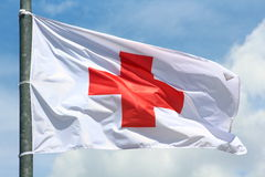 Red cross flag. Original photo red cross flag and symbol in the wind Stock Images