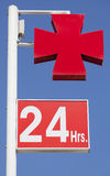 Red cross sign with 24 hours service outside medical clinic. Royalty Free Stock Photo