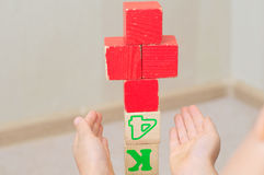 Red cross of toy cubes in kids hands Stock Photography
