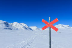 Red cross on a winter trail. Royalty Free Stock Images