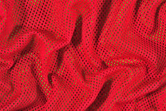Red crumpled nonwoven fabric on a green Royalty Free Stock Photos